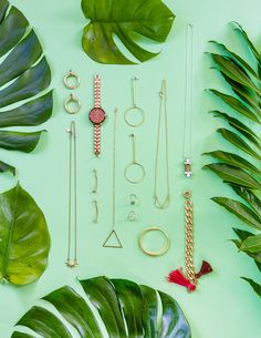 palm leaves flatlay with gold chain minimal jewellery on a green background. Click through to my blog to see my favourite pieces of jewellery.