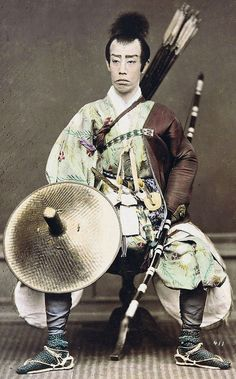 Samurai holding a yumi (bow) and wearing a yugote (shooting sleeves) over his left arm. Hand-colored photo, about 1870's or 1880̵...