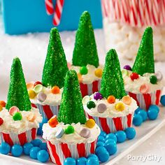 "Sprinkle candy ""presents"" on a forest of cupcakes! Click the pic to see how easy it is to make these cupcakes topped with edible Christmas trees."