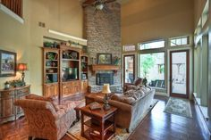 The cozy den offers high ceilings with wood beams as accent, stone fireplace and beautiful custom wood built-ins.