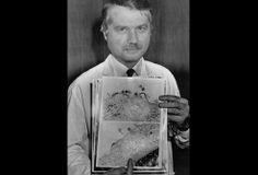 Dr. Luc Montagnier holds images of AIDS viruses