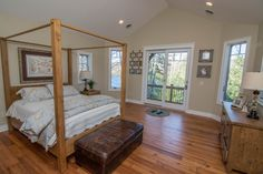 This master bedroom has tons of space and natural light, and we love all of the wood! It's also got a balcony overlooking Deep Creek Lake and a stunning master bathroom!