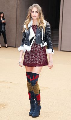 Cara Delevingne wearing patchwork over-the-knee boots, a lace dress and a fur trim motorcycle jacket during LFW.