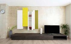 A TV em cima do rack, com a parede em outra cor é outra opção muito utilizada. Em uma sala grande, podem-se usar cores escuras
