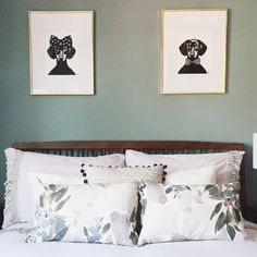 His and hers artwork above the bed in this pale teal bedroom.
