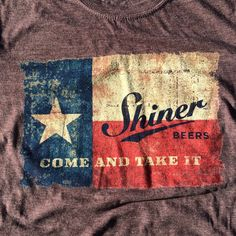 """#1 Best Seller The shirt is heathered brown with a rustic faded Texas flag in the background. """"Come & Take It"""" is located at the bottom of the flag area in bold writing. With a 65-35 blended fabric, t"""