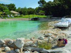 Paradis terrestre. Au Jas de l'Ange, maison d'hôtes provençale, cette impressionnante piscine de forme libre construite au pied des Alpilles joue l'intégration parfaite dans la roche environnante. Ponton en bois de sapin autoclave, eau chauffée, nage à contre-courant…