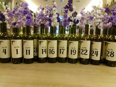 Wedding table numbers with wine bottles and lilac flowers.