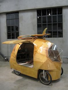Designed by SF-based artist Jay Nelson, the Golden Gate. Modern electric camper car made with fiberglass, epoxy resin, plywood, glass, bike parts, and an electric motor. Comes with a kitchen, stove, cooler, storage cubbies, toilet, bed, and storage below the bed.
