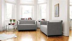 Modern grey sofa with wooden floors and white walls