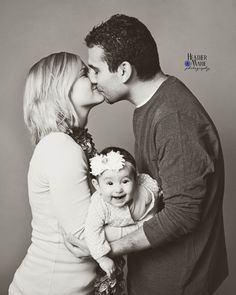Family pose with 6 month old baby.  Cute family pose with baby.  Black and white photography.  Studio photography.