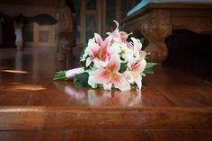 Bridal bouquet with pink lillies and white Thai orchids.