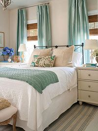 A soothing bedroom in pale blue green and white with a metal headboard and wood bedside table