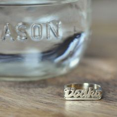 """For lovers of the potent clear stuff, this brass ring is for you. Tagged """"Vodka"""" in a carefully handcrafted script, this boozy ring is a personal ode to your poison of choice. Drink up, sweethearts."""