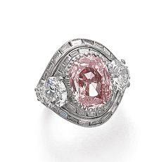 FANCY ORANGY PINK DIAMOND RING, GÜBELIN Centring on a cushion-shaped modified brilliant fancy orangy pink diamond weighing 4.12 carats, accented to either side with two graduated circular-cut diamonds, within a bombé surround of baguette diamonds