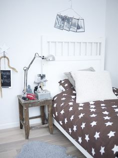 Boy's room. Brown star duvet, wire hanger picture holder, white walls and headboard, rustic side table.