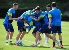 Up for it: The Arsenal squad play-fight during training ahead of the Champions League qual...