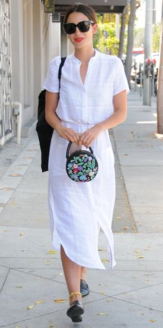 Lily Aldridge perfected her off-duty style in a breezy white cotton shirtdress that she expertly finished with a cute round floral purse, a yellow anklet, and black Jenni Kayne mules.