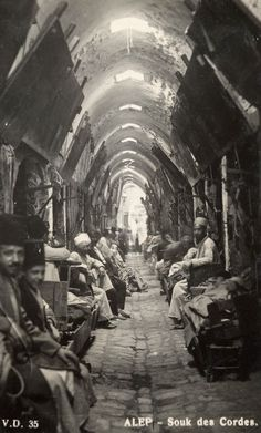 Aleppo Syria 1920 a real-photo postcard by Armenian photographer V. Deroian of shop owners sitting outside their individual stores at Aleppo's famous Souk el-...