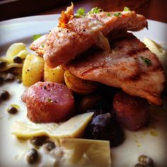 Grilled salmon with herb roasted potatoes and arugula in an artichoke and caper lemon sauce
