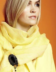 Sonnengelber Schal und Brosche mit eingefassten Kristallsteinen für einen schillernden Effekt.