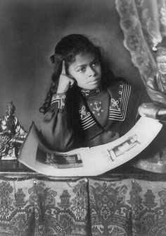 """Gorgeous little girl in amazing Victorian / Edwardian dress   Photo credit listed as """"African American Girl, Half-Length Portrait, with Right Hand to Cheek, with Illustrated Book on Table."""" 1899 or 1900. W.E.B. Du Bois Albums of Photographs of African Americans in Georgia Exhibited at the Paris Exposition Universelle in 1900, now in Library of Congress."""