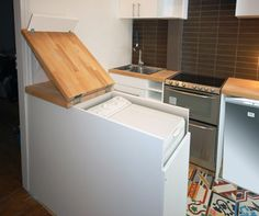 Parisian Architects Studio d'Archi came up with a smart solution, sticking a full-sized, top-loading washing machine in a kitchen island. The washing machine is fully concealed and accessible via a top-hinged butcher-block countertop. The lower panels come off permitting easy maintenance.