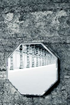 A collection of mirrors available in geometric shapes, framed by facetted silver-plated transparent glass.