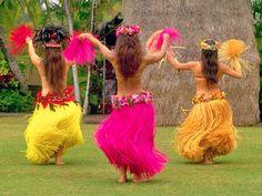 Hula dancers wearing beautiful colors... skirts swaying in unison. (Tahitian dancers)