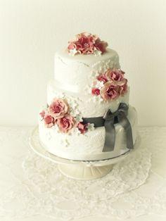 Romantische bruidstaart met grijs lint en bloemen