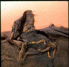 Photograph showing the W-cut neckline, and the remains of the collar. From the Guddal shirt (skjorte), dated ca. 1035- 1165 CE. Museum : Universitetsmuseet i Bergen,  InventoryNo : 030994,  Motif : Guddal-drakten, BRM 31/2, Fors. Retten. Hals/kr.,  Photographer : Ann-Mari Olsen.