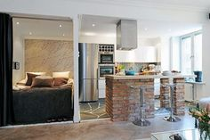 chambre salon aménagée avec un coin couchage, un coin cuisine avec bar petit déjeuner en brique
