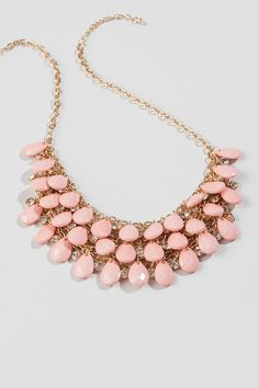 "Add a feminine touch to your look with the Brenham Teardrop Necklace in Pink.  Three rows of faceted, teardrop stones hang from golden chains, accented by round crystals.  Wear this with a ruffle sweater and crystal earrings for a great daytime outfit.<br /> <br /> - Finished with a lobster claw clasp<br /> - 29.5"" length<br /> - 3"" extension<br /> - Lead & nickel free<br /> - Imported"