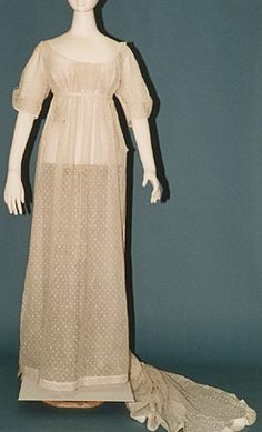 """1800-05 Diaphanous muslins, white on white embroidery. Think Greek or Roman draperies. Gathered bodice, still cut as one with gown. Moderately high bustline, gathered neckline, short or elbow length sleeves, train. Some overtunics. Hair dressed """"Greek fashion"""" towards the back of the head."""