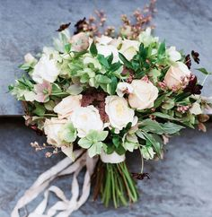 Loose clutch bouquets of ivory garden roses, white hellebore, ivory spray roses, purple lilacs, white ranunculus, lavender, cameilia foliage, and green nagi wrapped in ivory ribbon