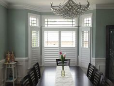 Beautiful dining room!  Love the chandelier and the bay window covered with our perfect view plantation shutters.
