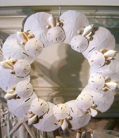 This wreath is made from pure white Florida sand dollars in two sizes with white chula shells and pearl umbonium. Add a raffia bow for year round use then change to an apple green, aqua or red ribbon bow for the holidays.