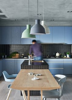 Sky blue cabinets are paired with a grey concrete ceiling and an island and backsplash clad in black mosaic tiles. Off the island is a wooden dining table with four different chairs.A Playful Apartment in Taiwan for a Modern Family Lifestyle - Design Milk Green Apartment, Apartment Design, Family Apartment, Cocinas Kitchen, Scandinavian Apartment, Scandinavian Design, Contemporary Interior Design, Design Interior, Cuisines Design