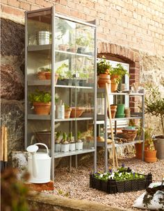 Ikea--A backyard with an outdoor cabinet with tempered glass doors and a shelving unit in steel.