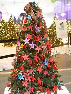 Paper Stars Christmas Tree:   This Christmas tree is an all-star! Simple blue, red, yellow, and purple paper stars, decorated and strung from colorful ribbons on a Christmas tree, look friendly and festive. Multicolor Christmas lights and a printed-ribbon tree topper add more color to this easily crafted Christmas tree.  Editor's Lighting Tip: Small twinkly lights and colored lights make more impact when you layer several strands and pair them with reflective ornaments.