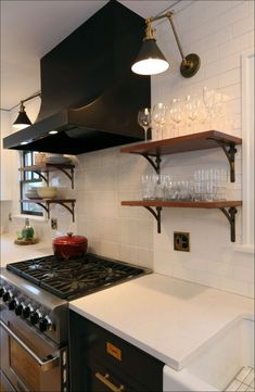 Modern kitchen. Open shelving. White subway tile backsplash, dark cabinets, white counters.