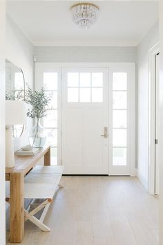 A white front door with six glass panels and sidelights open to a lovely foyer f. A white front door with six glass panels and sidelights open to a lovely foyer furnished with an iv Entry Door With Sidelights, Front Door Entrance, Wood Front Doors, Front Entry, Front Door Lighting, Entrance Foyer, Glass Panel Door, Glass Front Door, Doors With Glass Panels