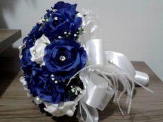 Buquê de flores em azul royal e off-white com broches prateados, pérolas, strass e outros adereços. <br> <br>Os buquês são personalizados e montados de acordo com o gosto da noiva. <br> <br>Eles são únicos sendo que nunca existirá um buque idêntico ao outro. <br>Composto de broches em tons de prata cravejados em strass, flores de cetim e pérolas. <br> <br>Possui 22cm diâmetro <br> <br>