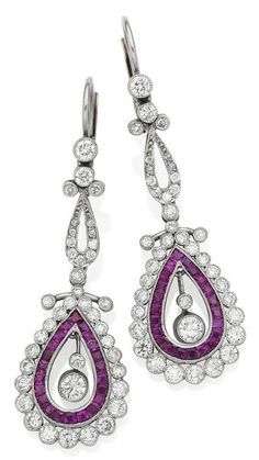 A pair of early 20th century ruby and diamond pendent earrings. The drop-shaped openwork plaques, millegrain-set with calibré-cut rubies and graduated old brilliant-cut diamond collets, the articulated diamond collet centres to the similarly-set diamond surmounts, later fittings, diamonds aprroximately 1.40 carats total, length 5.0cm