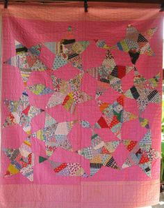 """Spiderweb Stars, feedacks and cotton novelty prints, back is a lighter pink cotton brought to the front for the binding. 80"""" x 66"""", hand-quilted in the elbow fashion."""