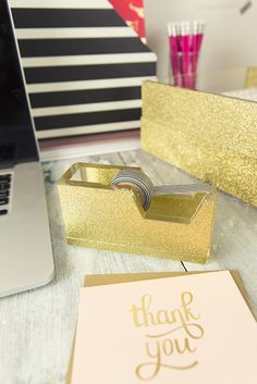 """You will be the talk of the town (or at least the office) with this glittery tape dispenser! -Made of heavy cast polished acrylic -Dense gold glitter -Industrial glitter, won't rub off! -Holds all tape up to 3/4"""" wide -Non-skid feet"""