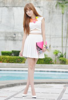 Cut out top + white pleat skirt + white heels + neon clutch + neon necklace.