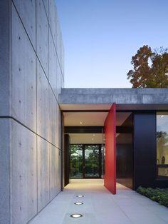 Porta pivotante colorida, em uma fachada de concreto.  Fotografia: http://www.decorfacil.com/portas-pivotantes/