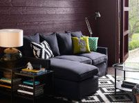 mix of patterns. horizontal walls with diamond shapes on rug and pillows. solid, dark colors keep things cozy coupled with soft lamp-lights
