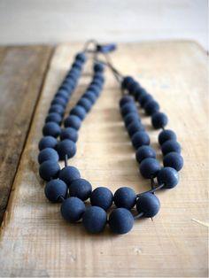 Myriam Balaÿ Devidal, diplômée des Beaux arts de Saint Etienne mélange le papier le textile et le bois pour créer des objets insolites de toute sorte. Le Graaand collier perles de bois indigo monté sur élastique noir. Taille: 85cm